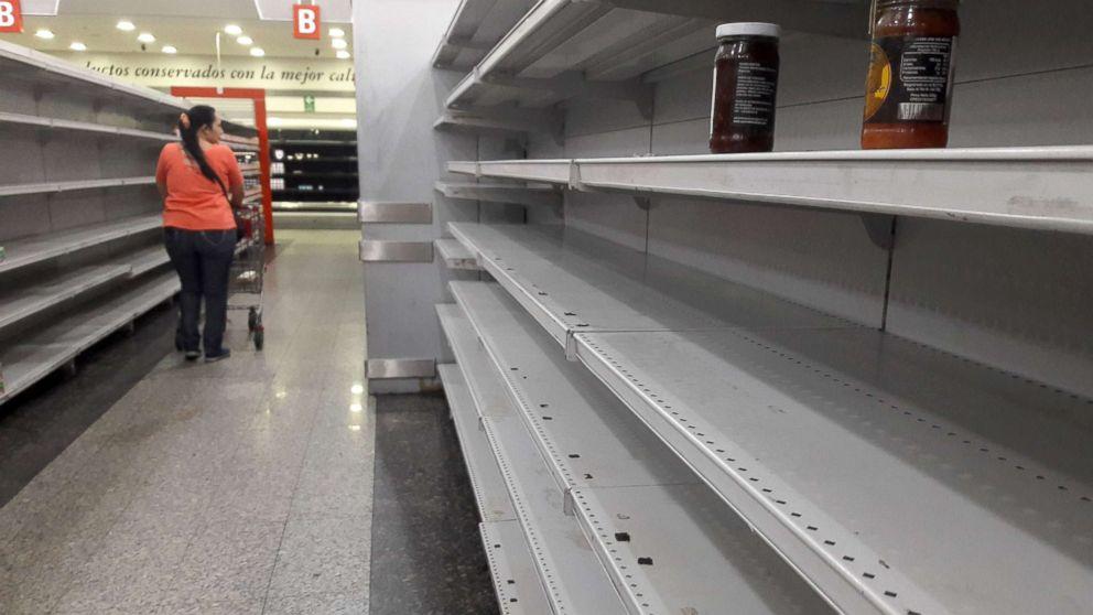 A woman walks between the empty shelves of a supermarket in Caracas, Venezuela, Jan. 11, 2018.