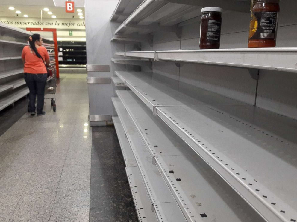 PHOTO: A woman walks between the empty shelves of a supermarket in Caracas, Venezuela, Jan. 11, 2018.