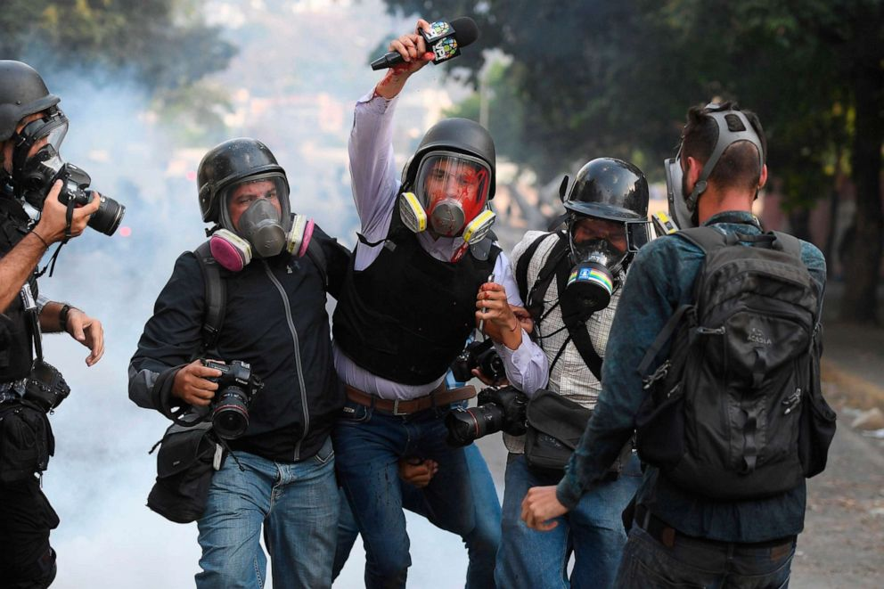 PHOTO: Venezuelan journalist Gregory Jaimes, center, is assisted by colleagues after being injured during clashes between anti-government protesters and security forces during the commemoration of May Day on May 1, 2019.