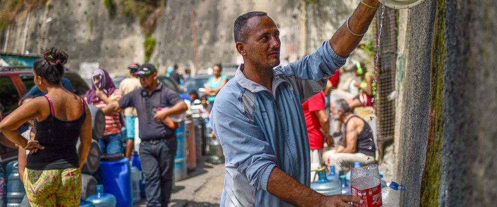 """PHOTO: A man fills containers with water flowing down from the Wuaraira Repano mountain, also called """"El Avila"""", in Caracas, March 13, 2019."""
