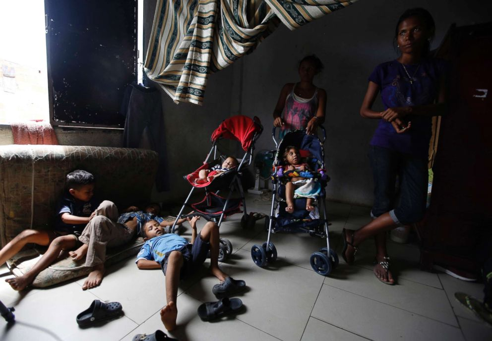 PHOTO: Venezuelan children are watched over by a few of their mothers while others work, inside a sparsely furnished home shared by about 10 people in Cucuta, Colombia, June 27, 2018.