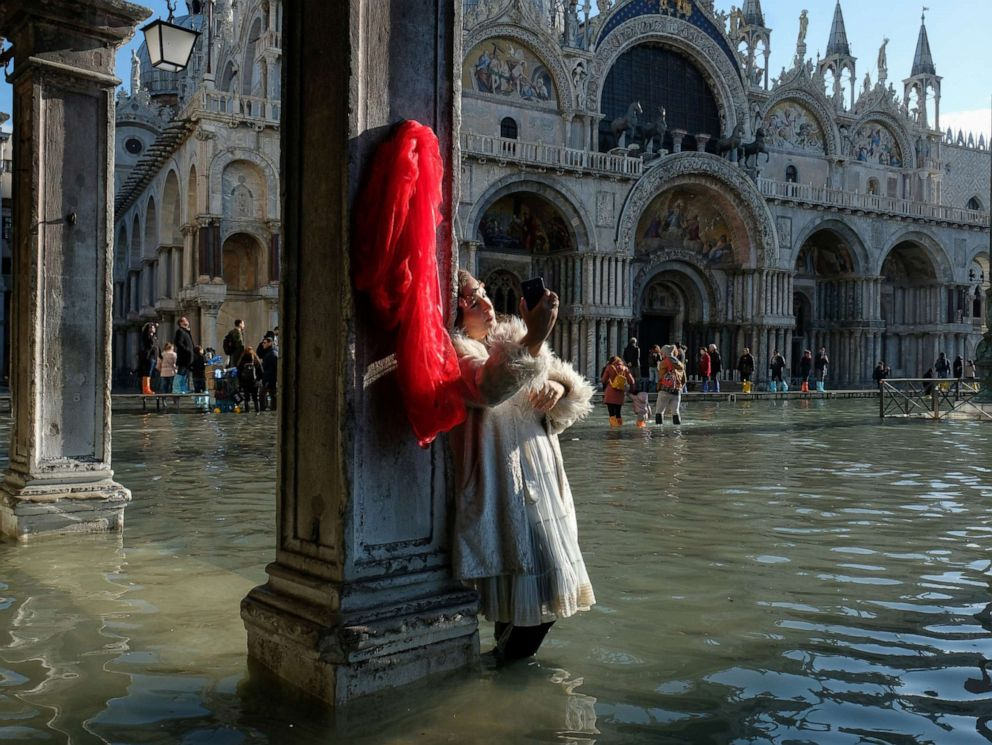 PHOTO: A woman takes pictures in the flooded St. Marks Square during a period of seasonal high water in Venice, Italy, Nov. 14, 2019.
