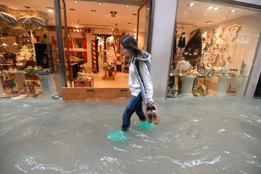 A woman walks in a flooded street of Venice, Italy, Monday, Oct. 29, 2018.