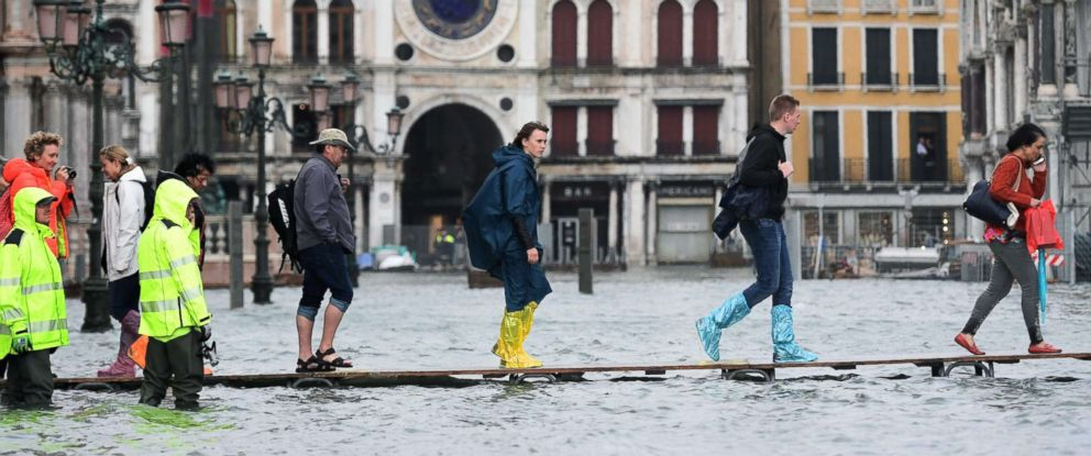PHOTO: People walk on a footbridge in the flooded St. Marks Square during a high water alert in Venice on Oct. 29, 2018.