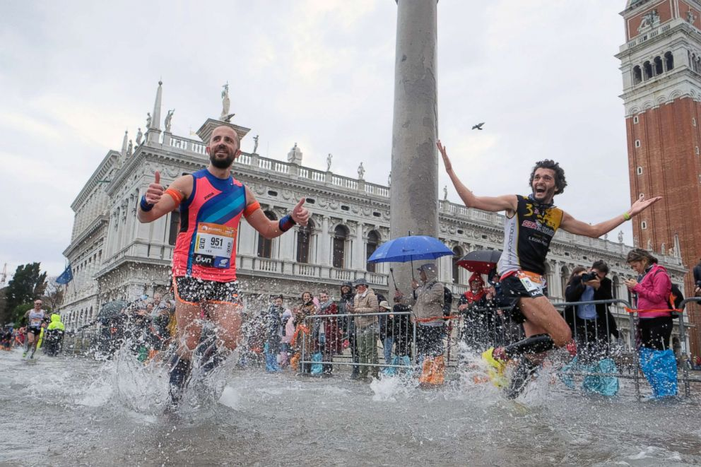 People run in the 33rd Venice Marathon during high tides in Venice, Oct. 28, 2018.