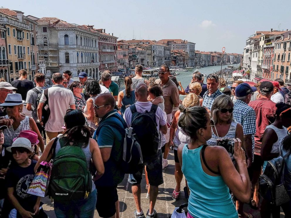 PHOTO: A large crowd of tourists stand on the Rialto bridge, Aug. 1, 2017, in Venice, Italy.