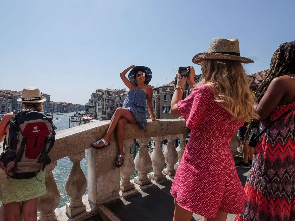 PHOTO: A tourist takes a picture of one of her friends at the top of Rialto bridge on Aug. 1, 2017 in Venice, Italy.