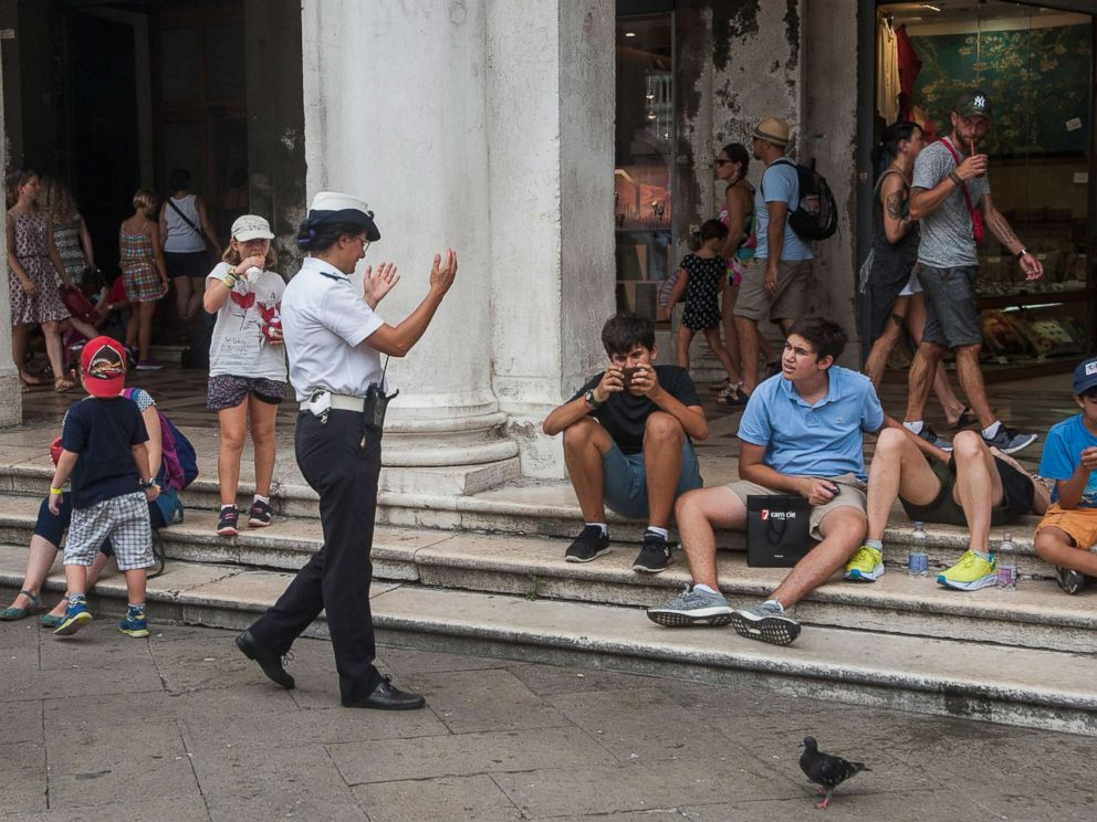 PHOTO: A local police officer tells tourists to move away from Saint Marks Square on Aug. 14, 2017 in Venice, Italy.