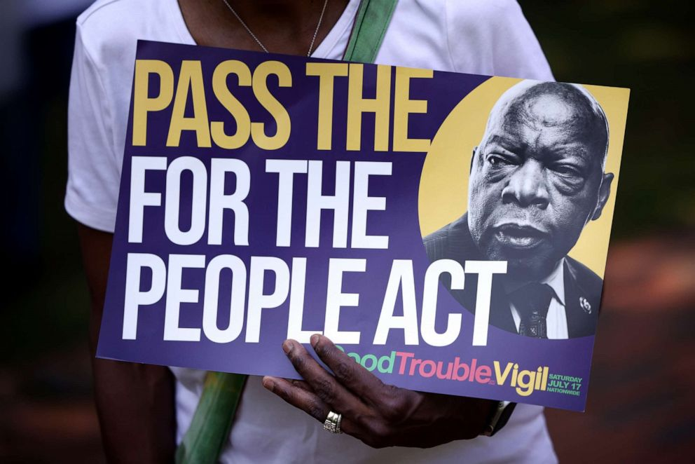"""PHOTO: A voting rights activist holds a sign that reads """"Pass The For The People Act"""" during a voting rights rally outside the White House, Aug. 24, 2021, in Washington, DC."""