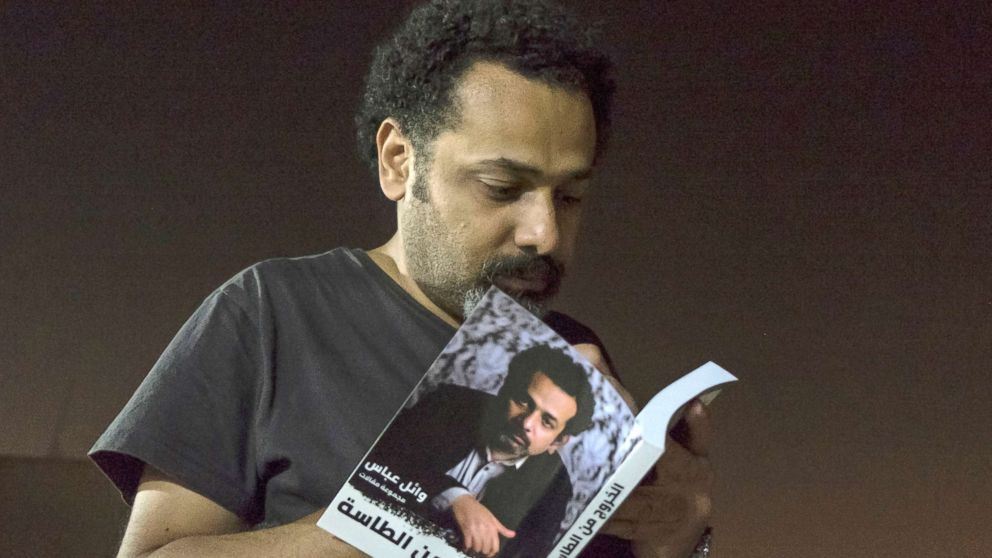 """In this June 9, 2017 file photo provided by Roger Anis, prominent activist and blogger Wael Abbas signs a copy of his book, """"The theory of leaving the bowl,""""?� in Cairo. Egyptian security officials said Abbas, known for documenting police abuse, was detained, Wednesday, May 22, 2018, the latest in a new wave of arrests since elections earlier this year."""