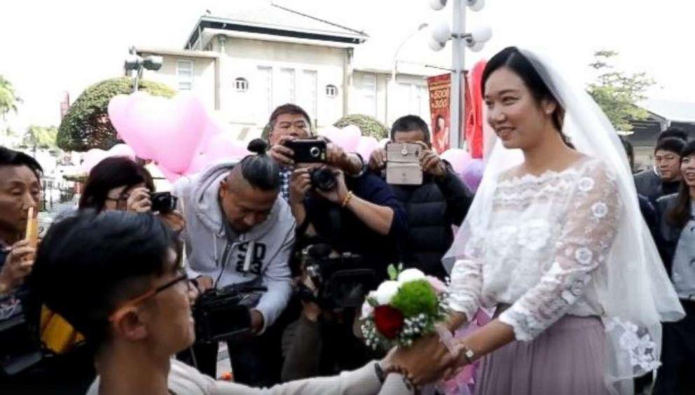A newlywed couple celebrates the new walk signal.