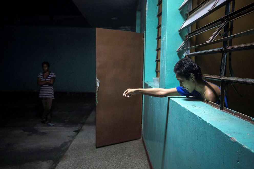 PHOTO: A mental health patient leans out of her room at the Caracas Psychiatric Hospital, in Caracas, Venezuela, July 14, 2019.