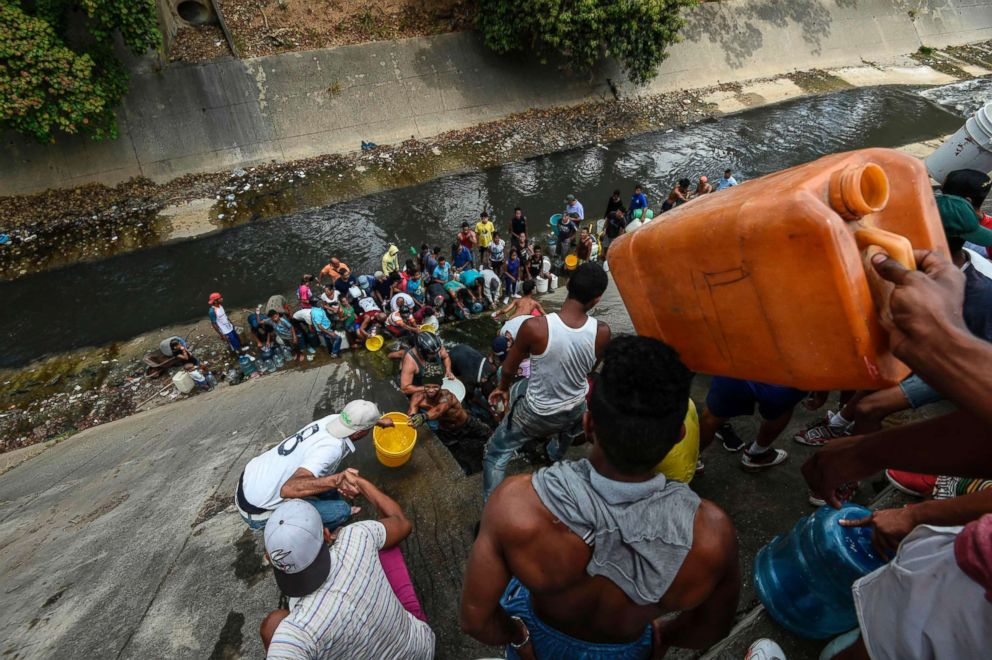 People collect water from a broken pipe, flowing into a sewage canal at the Guaire river in Caracas, Venezuela, March 11, 2019, as a massive power outage continues affecting some areas of the country.