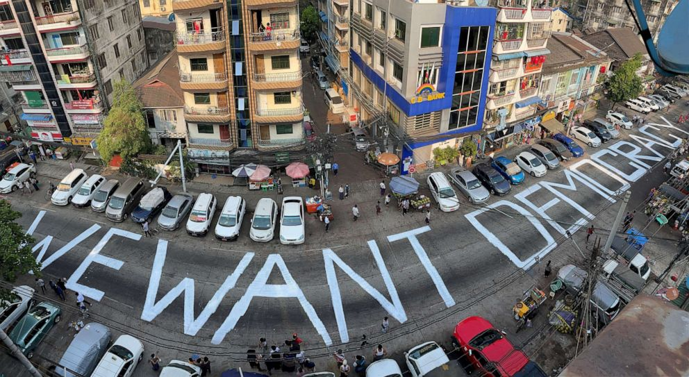 """PHOTO: A slogan that reads """"We Want Democracy"""" is written on a street to protest the military junta in Yangon, Myanmar, on Feb. 21, 2021."""