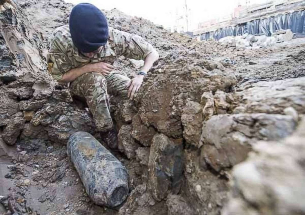 A British Army bomb disposal expert inspects an unexploded German bomb dating back to World War II on May 21, 2015 in Wembley 200 meters from the soccer stadium in London.