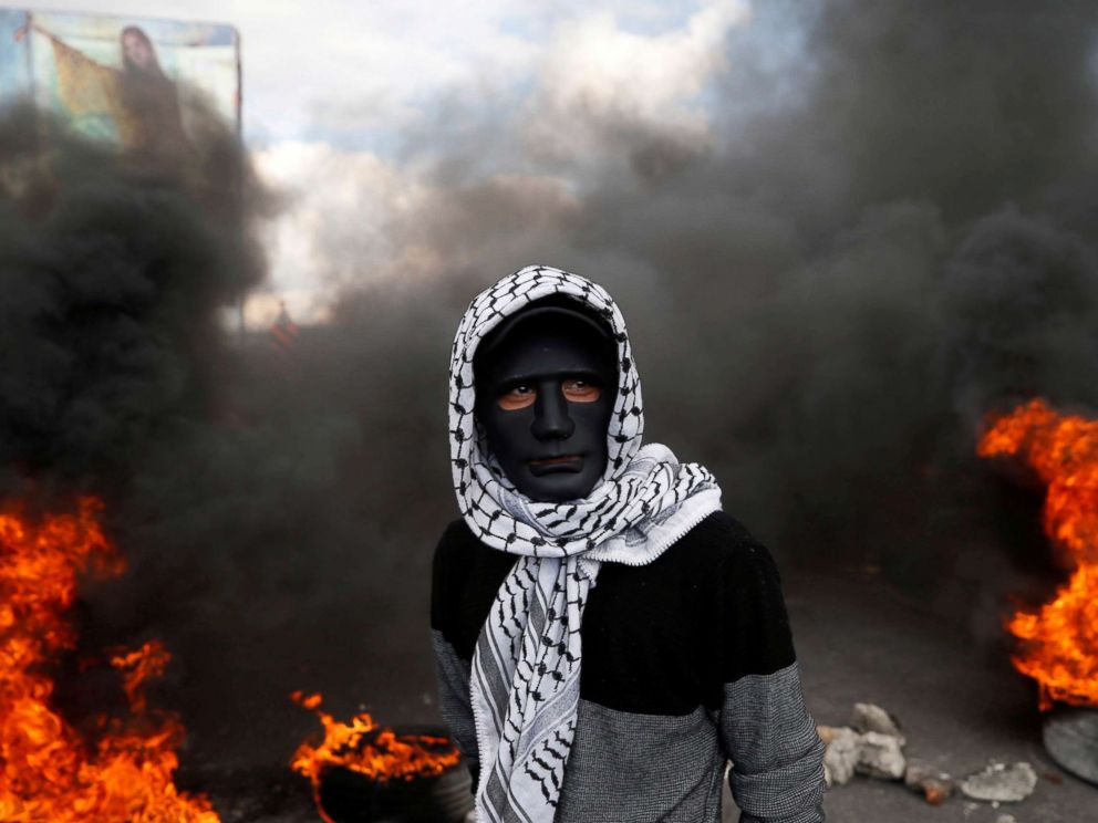 PHOTO: A Palestinian demonstrator stands near burning tires during clashes with Israeli troops at a protest against President Donald Trumps decision to recognize Jerusalem as the capital of Israel, near the West Bank city of Nablus, Dec. 15, 2017.