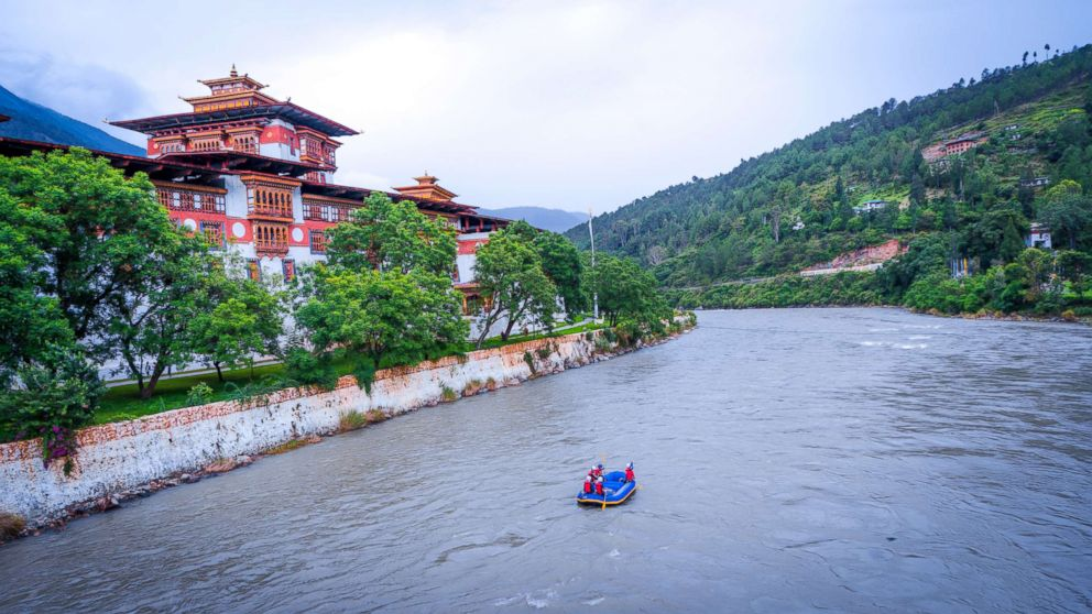 PHOTO: A waterway patrol passes by the Punakha Dzong, which was constructed in 1638, at the convergence of the Pho Chhu (father) and Mo Chhu (mother) rivers.
