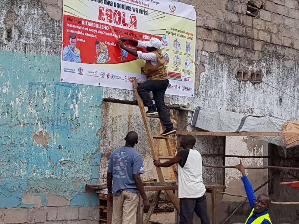 PHOTO: Social mobilizers put up an Ebola poster in Tchomia to raise awareness in the local community in the Democratic Republic of Congo, Oct. 9, 2018.