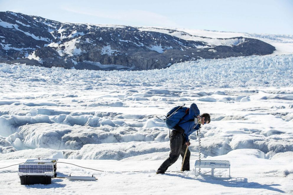 PHOTO: Safety officer Brian Rougeux uses a drill to install antennas for scientific instruments that will be left on top of the Helheim glacier near Tasiilaq, Greenland, June 19, 2018.