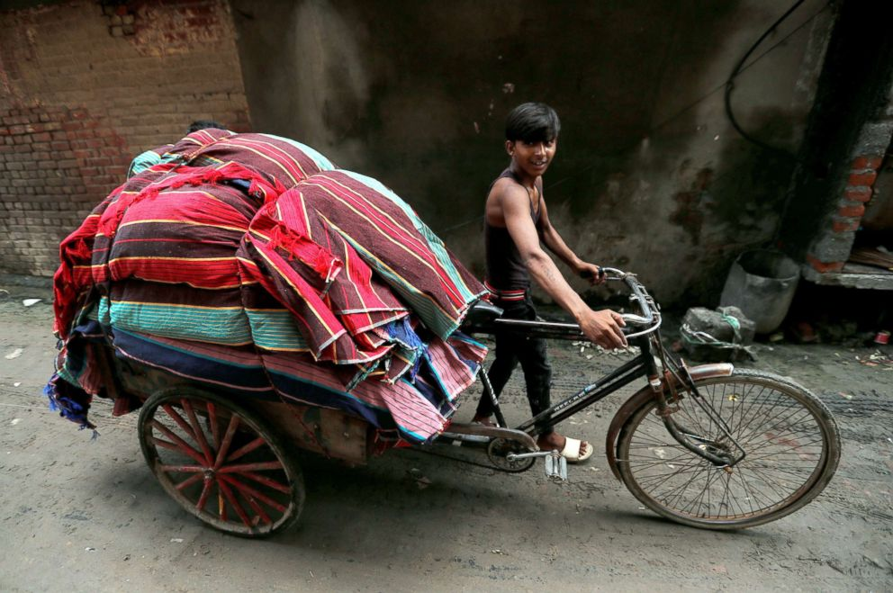 A man carries rugs on a rickshaw in an industrial area in Panipat, India, Aug. 24, 2018.