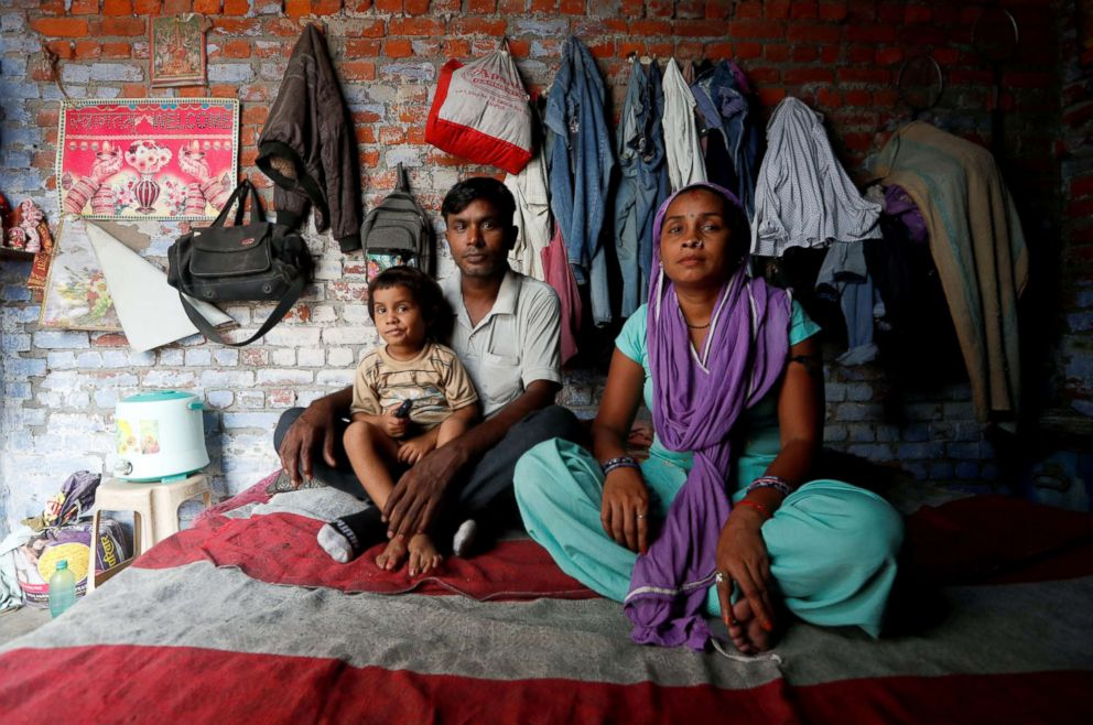 Ram Pratap who lost his job as a powerloom operator earlier this year, poses for a portrait with his wife and daughter inside his house in Panipat, India, Aug. 24, 2018. After losing his job as an operator, Pratap started working as a clerk and a caretaker at another weaving factory.