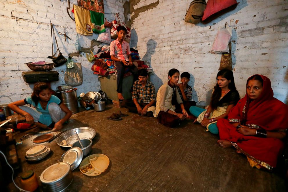 PHOTO: Dilip Soni, third from left, who lost his job as a power loom operator earlier this year and now works as a packaging labour, sits with his family as they wait to have their lunch in Panipat, India, Aug. 29, 2018.