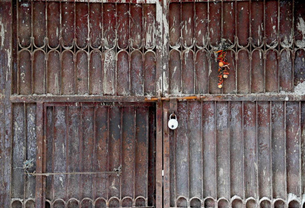 A locked gate of a weaving factory, that was shut a year ago, is seen in Panipat, India, Aug. 29, 2018.