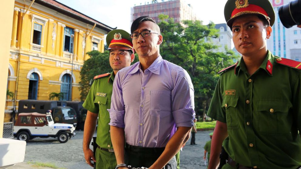 American-Vietnamese citizen William Nguyen (C) is escorted by policemen to a courtroom for his trial in Ho Chi Minh City on July 20, 2018.