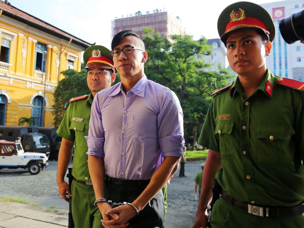 PHOTO: American-Vietnamese citizen William Nguyen (C) is escorted by policemen to a courtroom for his trial in Ho Chi Minh City on July 20, 2018.