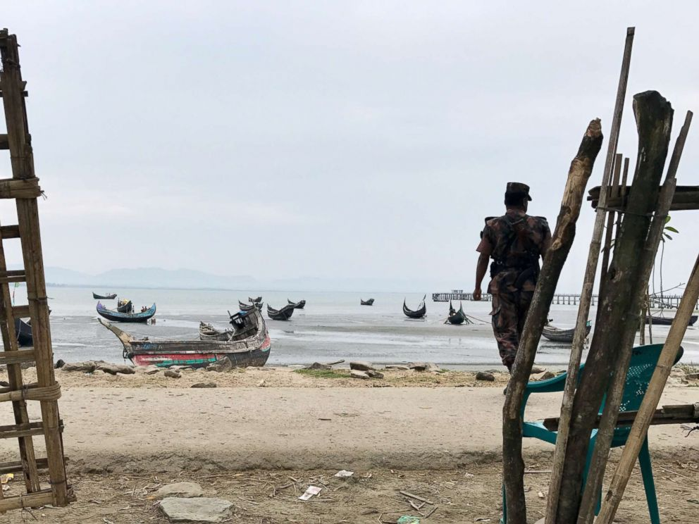 PHOTO: Guards wait on the shores of Bangladesh, at Shah Porir Dwip Island. Rohingya fleeing Myanmar arrive here first.