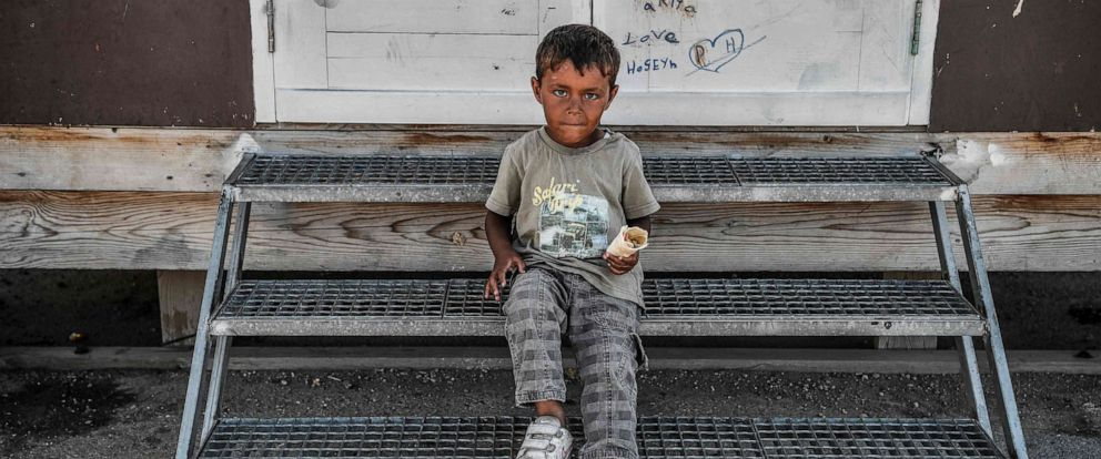 PHOTO: A boy sits at the entrance of a prefab at the Skaramangas refugee camp, on the outskirts of Athens, on June 5, 2019.