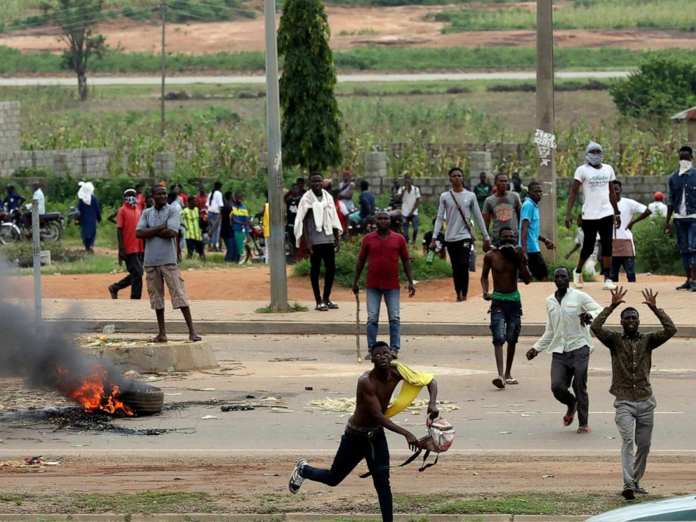 PHOTO: Protesters throw rocks at policemen during an attack on South African business, in Abuja, Nigeria, Sept. 4, 2019.