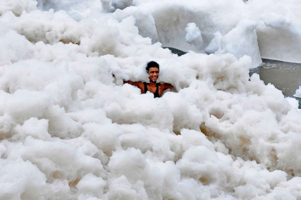 A man immerses himself in a large amount of toxic foam formed along the banks of the Yamuna on July 12, 2015, in Noida, India. The pollution is caused in part to high ammonia levels emanating from the high discharge of industrial pollutants in the river.