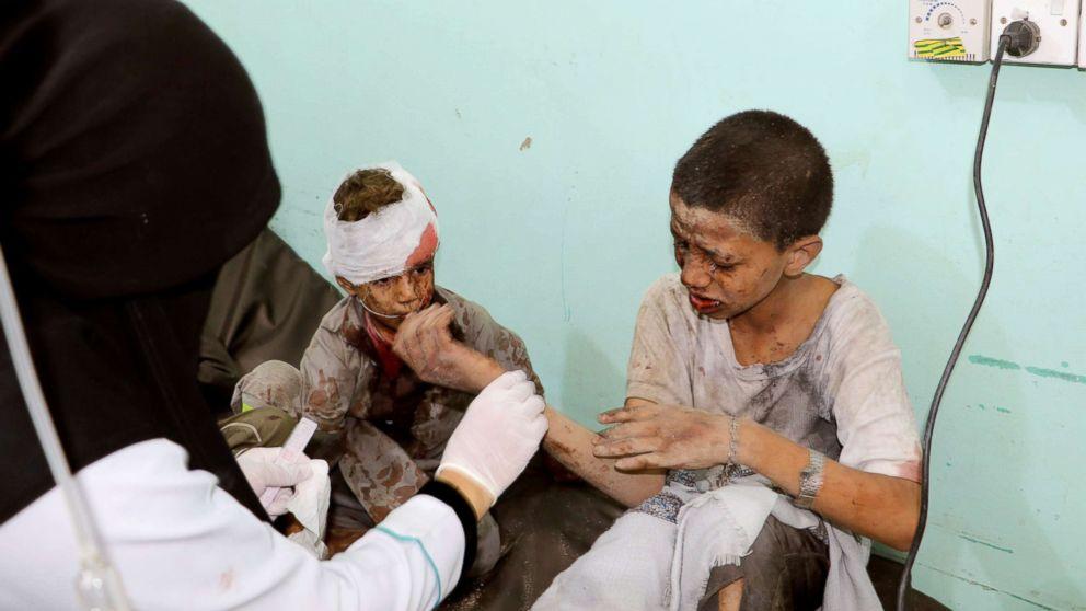A doctor treats children injured by an airstrike in Saada, Yemen Aug. 9, 2018.