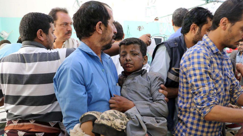 A Yemeni man holds a boy who was injured by an airstrike in Saada, Yemen Aug. 9, 2018.