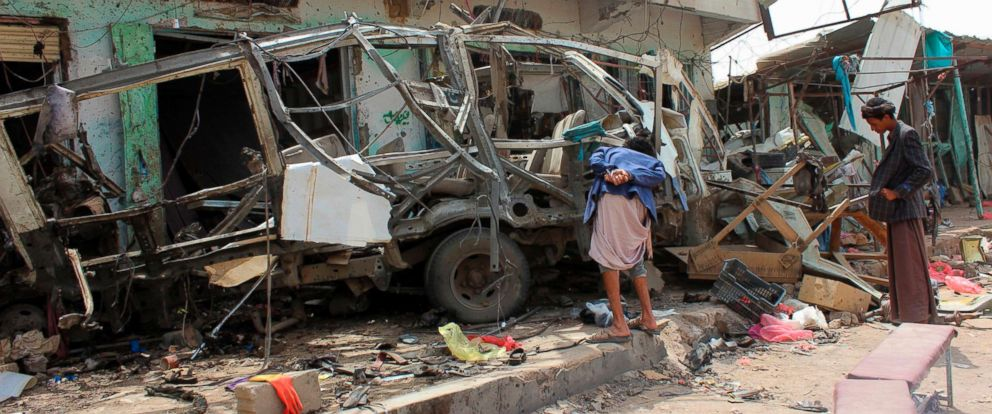PHOTO: Yemenis gather next to the destroyed bus at the site of a Saudi-led coalition air strike, that targeted the Dahyan market the previous day in the Huthi rebels stronghold province of Saada, Aug. 10, 2018.
