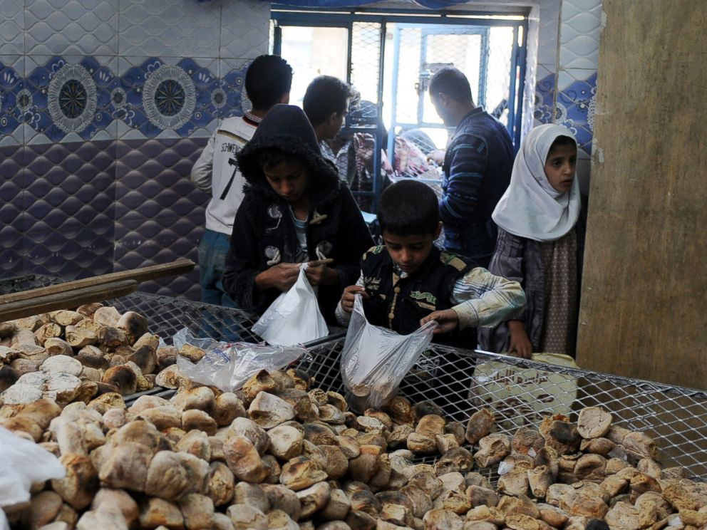 PHOTO: Children distribute free bread to people at a center financed by rich people and merchants in Sanaa, Yemen, Nov. 12, 2017.