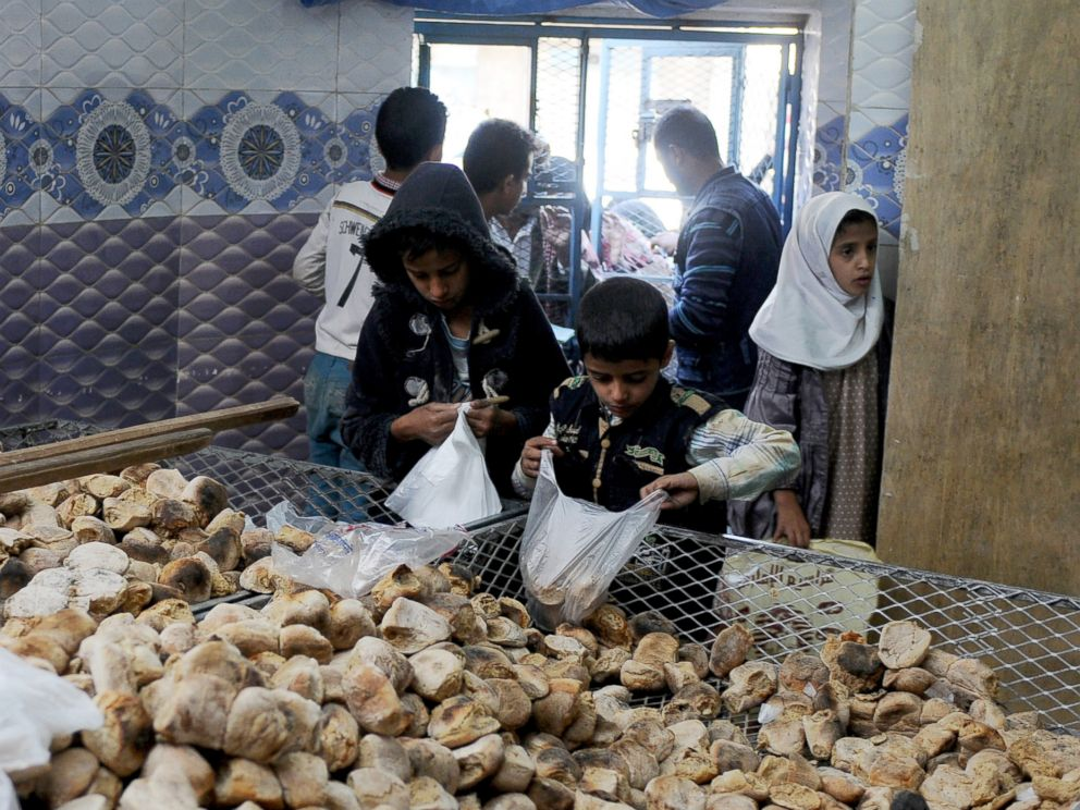 PHOTO: Children distribute free bread to people at a center financed by rich people and merchants in Sanaa, Yemen, on Nov. 12, 2017.