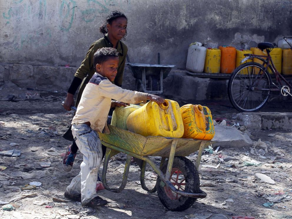 PHOTO: Yemeni children push a wheelbarrow with jerrycans filled with drinking water from a donated water pipe in Sanaa, Yemen, Nov. 18, 2017.