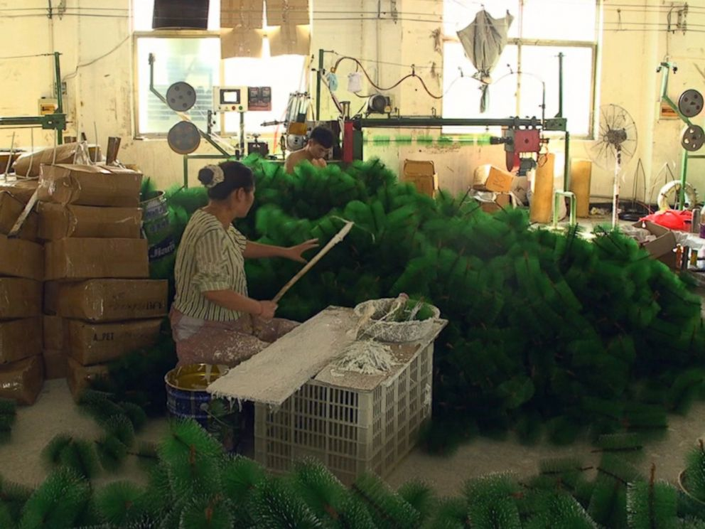 photo a factory worker in yiwu china assembles christmas trees for the upcoming holiday - Christmas Village Decorations
