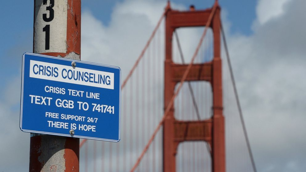 A suicide prevention sign is posted at the Golden Gate Bridge, on April 13, 2017, in San Francisco. Local officials gathered Thursday at the orange-red span to mark the beginning of work to line both sides of the bridge with steel netting.