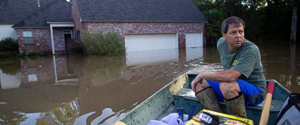 PHOTO: David Key boats away from his flooded home after reviewing the damage in Prairieville, Louisiana, Aug. 16, 2016.