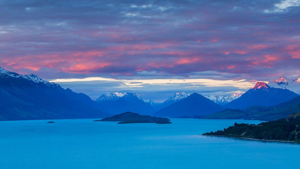 Mount Earnslaw and neighboring mountain peaks in the Southern Alps are lit with the last rays of the sun beyond Lake Wakatipu, Otago in South Island, New Zealand in this undated stock photo.