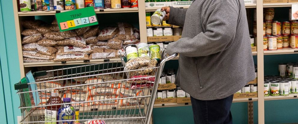 PHOTO: A woman adds canned vegetables to her cart at a food pantry in this file photo.