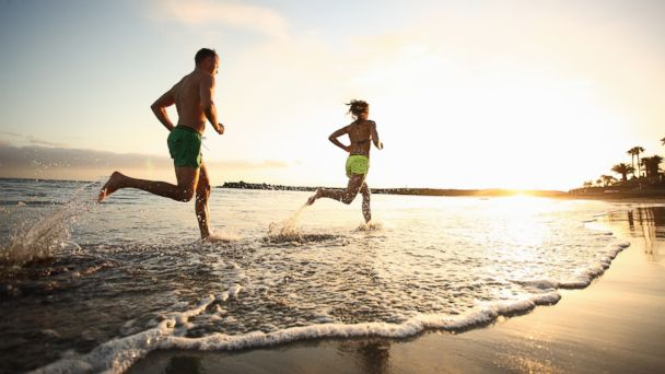 PHOTO: A man and woman run on beach at sunset.