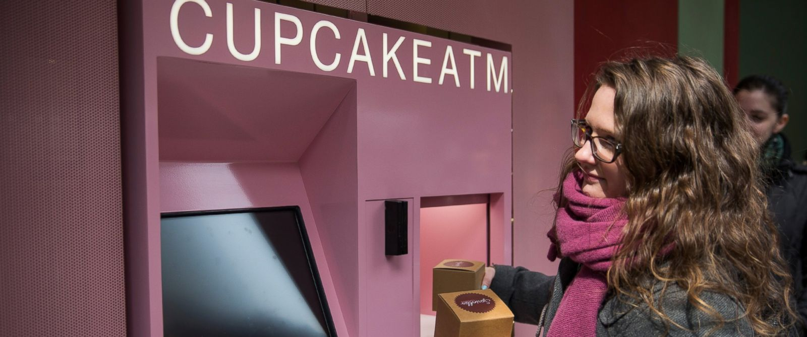 """PHOTO: A woman takes her order after using the """"Cupcake ATM"""" created by Sprinkles Cupcakes"""