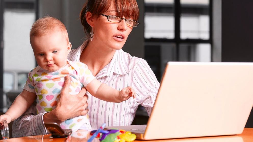 A mother holds her baby while working on a laptop in this stock photo.