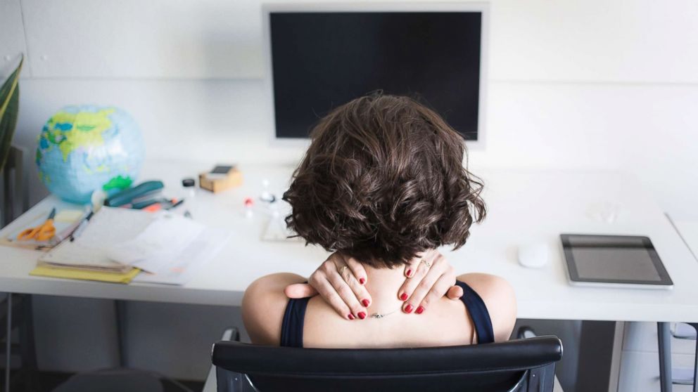 A young woman massages her neck at a desk in an undated stock photo.