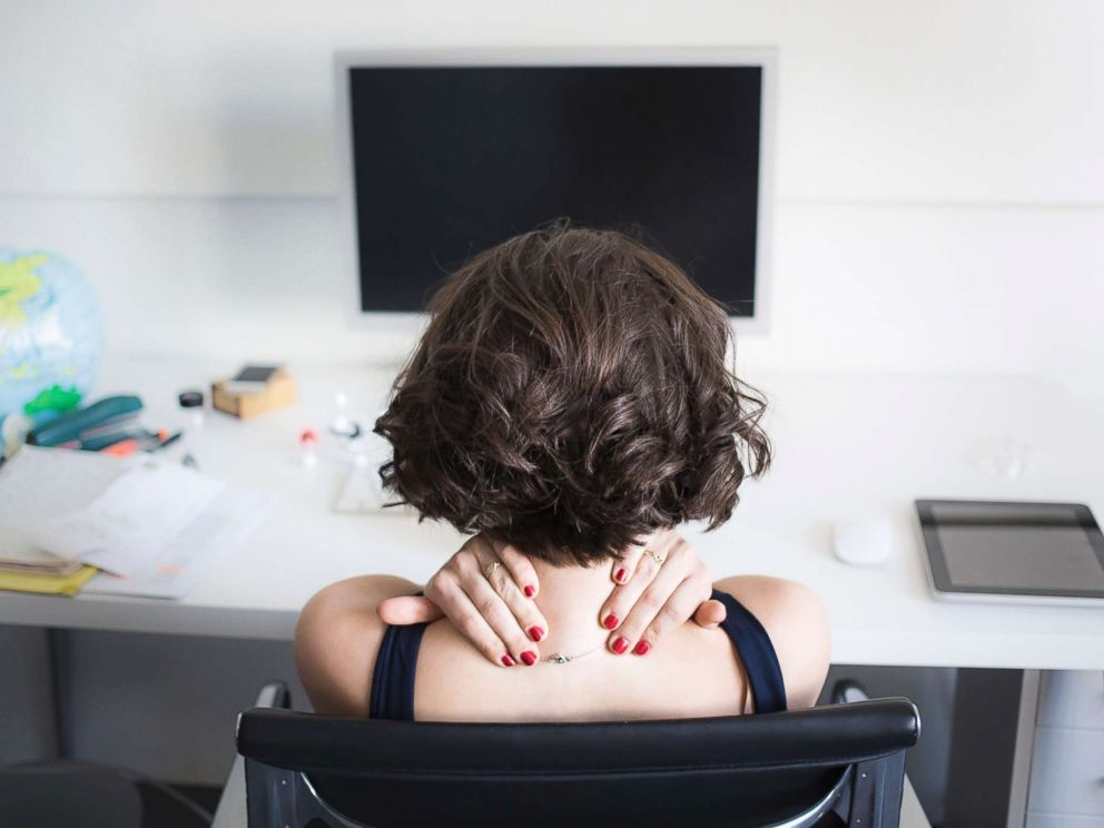 PHOTO: A young woman massages her neck at a desk in an undated stock photo.