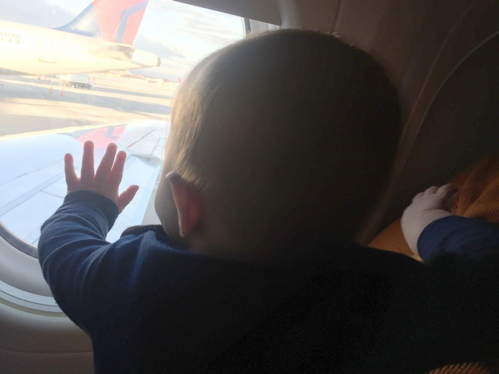 PHOTO: Evan Hughes of Fort Worth, Texas, shared a photo of his 8-month-old son, Ki, being held on a Dallas-bound plane flight by India Massinburg, a stranger who offered to help.